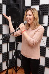 Девушка в свитере учится правильно петь