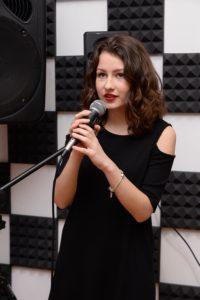 Девушка в черном платье проходит обучение в вокальной студии