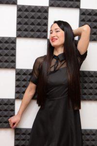Брюнетка в черном платье в студии вокала