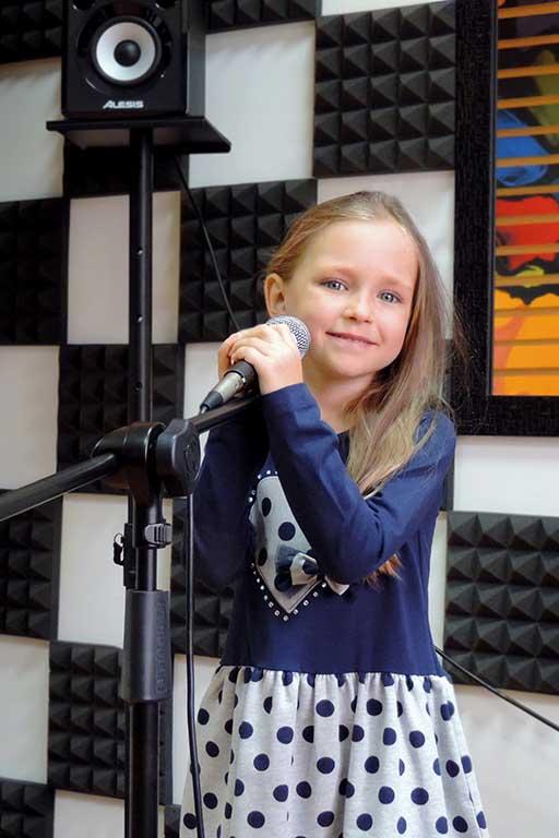 Маленькая девочка учится петь