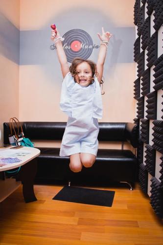 Девочка в синем платье прыгает на фоне логотипа MELOS MANIA