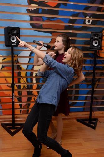 Преподаватель по вокалу в синем учит петь девушку