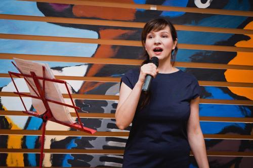 Женщина в синем платье поёт